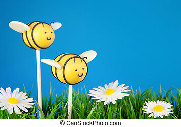 Bee cake pops - Mini cakes on sticks dipped in colored...