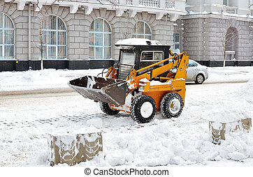 yellow tractor cleaning the snow on a street