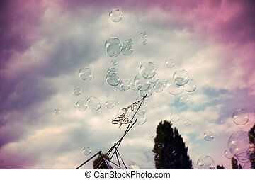 An anonymous man making giant soap bubbles on an early...
