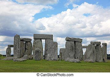 Stonehenge historic site on green grass under blue sky....