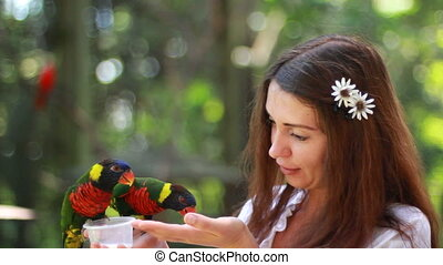 Smiling girl with colorful parrot in the jungle