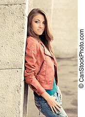 Happy young girl in red jacket - Young woman wearing jeans...