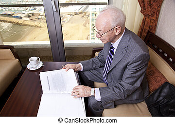 An elderly (in his 80's) business man wearing suit and tie sitting in a hotel's business lounge, going over some papers after having coffee. The seashore and a marina can be seen defocused in the ba