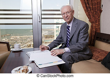 An elderly (in his 80's) business man wearing suit and tie sitting in a hotel's business lounge, looking at camera with a slight smile on his face, in the middle of going over some papers after havi