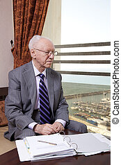 Senior Businessman Looking Out the Window - An elderly in...