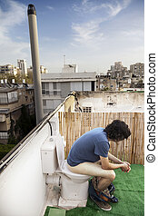 Using Rooftop Lavatory - Caucasian adult man in his early...