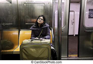 Woman with Suitcase in New-York Subway - An adult woman with...