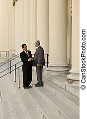Attorney and Client - Two men shaking hands on courthouse...