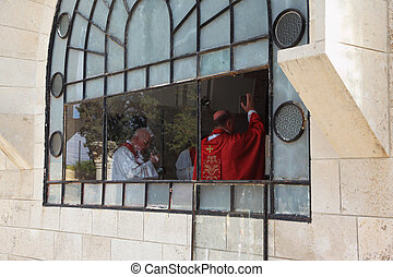 Cleric in a red mantle blesses parishioners - Worship in the...