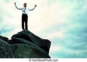 highest achievement - Successful business man standing on a...
