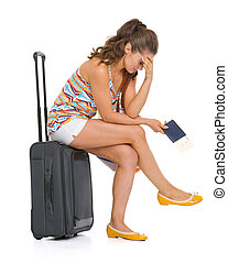 Stressed young tourist woman sitting on wheel bag