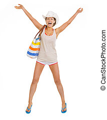 Happy young beach woman in hat jumping