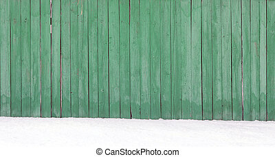 Old wooden fence in a snow drift
