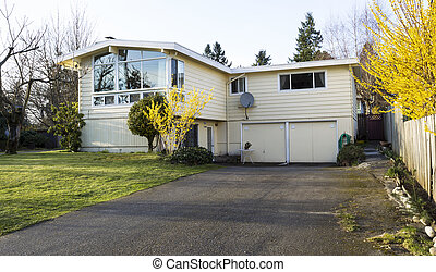 Horizontal photo of older residential home in early spring with large driveway, front yard and bare trees