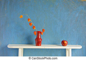 red apple and dry husk tomato flowers in vase - still-life...