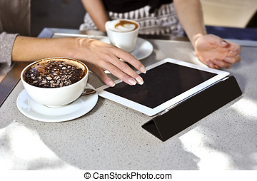 two friends use a digital tablet whilst enjoying a coffee at...