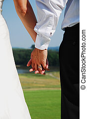 wedding hands - holding hands with wedding rings together