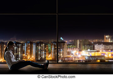 young woman sitting with a laptop by the window with a night...