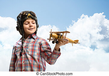 Boy in helmet pilot playing with a toy airplane - Boy in...