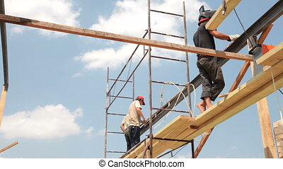 Roofing works - Builders on scaffolds construct roof of the...
