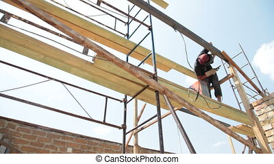 welder working on the scaffold - Roofing works - welder...