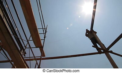 Roofing works - worker on scaffold - silhouette of worker on...