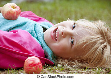 Happy girl with apples lying on the grass outdoors