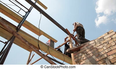 Roofing works - workers on scaffold - construction workers...