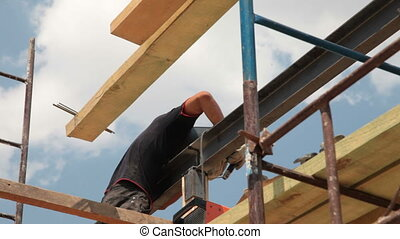 Roofing works - welder working on the scaffold