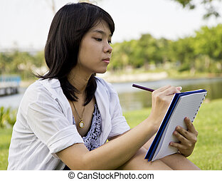 Girl writing a book in the park.