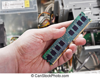 RAM in hand on a background of the disassembled system unit