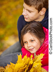 Children playing with autumn fallen leaves