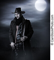 Handsome man in cowboy costume stay in steppe at night with...