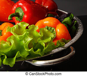 Freshly washed fresh vegetables in a metal colander isolated...