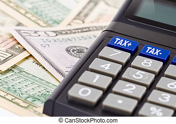 Calculating Tax - Tax calculator on a pile of US dollar...