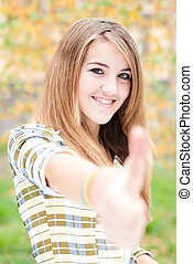 Teenage girl showing thumb up on autumn day - Smiling...