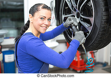 Mechanic changing wheels on a car on hydraulic ramp -...