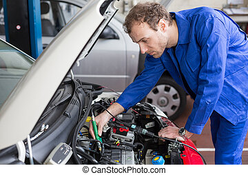 Mechanic repairing a car in a workshop or garage - Mechanic...