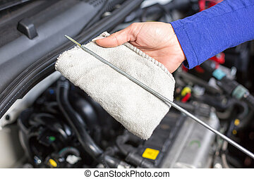 Car mechanic taking a look at the oil level - Car mechanic...