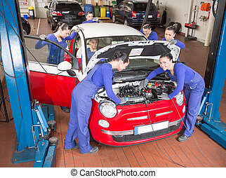 Multiple Auto mechanics repairing a car in garage - Auto...