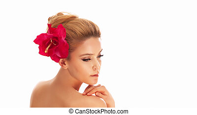 Close-up photo of young blonde beauty with red flower in hair. Looking away. Long lashes. Profile portrait.