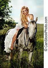 Young blonde bride riding a horse in fashionable dress. -...