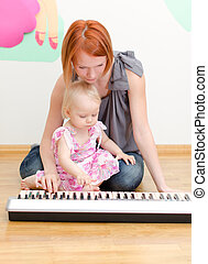 Little girl and her mother playing the piano