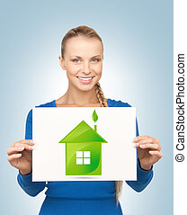 woman with illustration of green eco house - woman holding...