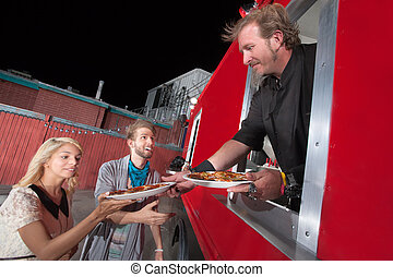 Serving Carryout Pizza from Food Truck - Chef serving...