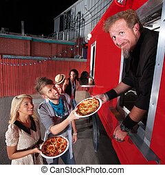Pizza Dinner at Food Truck - Food truck owner serving pizza...