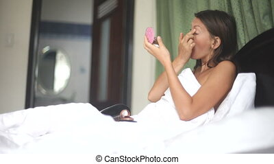 young beautiful woman listening music using mobile phone on bed