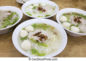 Bowls of Southeast Asian Fishball Noodle Soup with Pork...