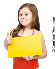 Little girl is holding blank yellow banner and showing thumb...