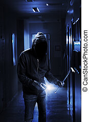 Burglar with flashlight and crow bar in a dark office...